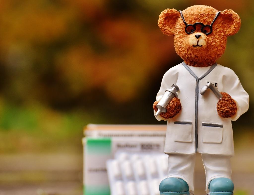 Ein Porzellanbär mit Arztkleidung. Im Hintergrund ist verschwommen eine Packung Medikamente.