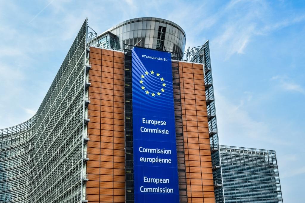 Das Gebäude der Europäischen-Kommission. Ein hohes modern wirkendes Gebäude vor dem ein blauer Banner hängt. Auf dem Banner steht in verschiedenen Sprachen Europäische Kommission. Darüber der Sternenkranz der EU und ganz oben in weißer Schrift #TeamJunkerEU