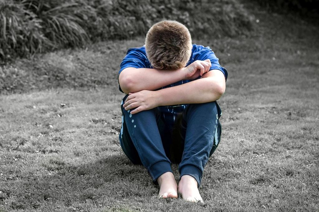Ein Junge sitzt Barfuss im grauen Gras. Seinen Kopf vergräbt er in seinen Armen. Er wirkt traurig.
